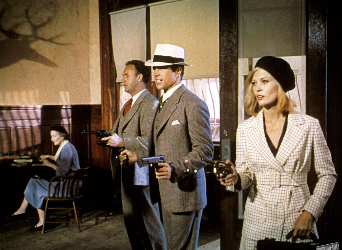 Medium shot in bank of Gene Hackman as Buck Barrow, Warren Beatty as Clyde Barrow, wearing hat, and Faye Dunaway as Bonnie Parker, all holding guns/pistols; woman seated in background. PHOTOGRAPHS TO BE USED SOLELY FOR ADVERTISING, PROMOTION, PUBLICITY OR REVIEWS OF THIS SPECIFIC MOTION PICTURE AND TO REMAIN THE PROPERTY OF THE STUDIO. NOT FOR SALE OR REDISTRIBUTION. ALL RIGHTS RESERVED.